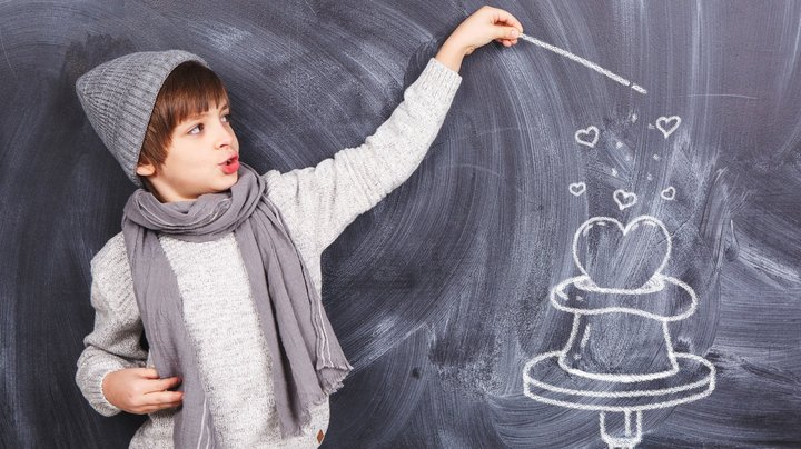 Junge vor Tafel zaubert ein mit Kreide gemaltes Herz aus einem mit Kreide gemalten Hut.