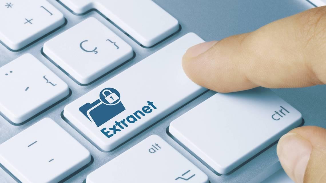 """Der Zeigefinger eines Nutzers drückt die Eingabetaste einer Tastatur, auf der """"Extranet"""" geschrieben steht"""