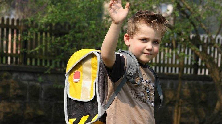 Schulkind mit Schulranzen winkt in die Kamera