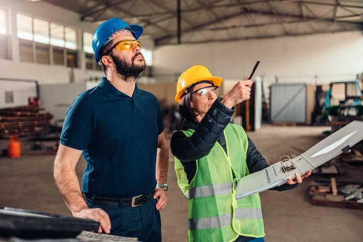 Fachkraft für Arbeitssicherheit beurteilt Arbeitsbedingungen in Lagerhalle