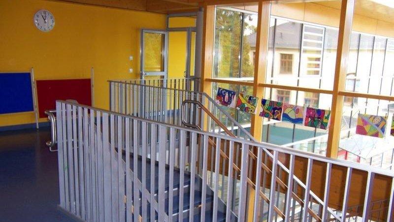 Blick in das Treppenhaus eines Schulgebäudes, im Hintergrund große Fenster