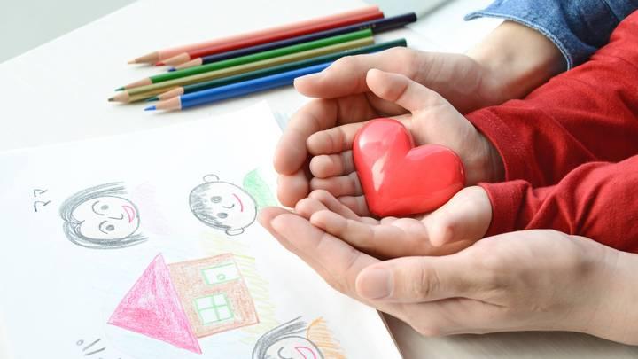 Ein von einem Kindt gemaltes Bild mit Buntstiften zeigt eine Familie und ein Haus. Ein Paar Erwachsenenhände hält ein paar Kinderhände. In den Kinderhänden liegt ein rotes Herz.