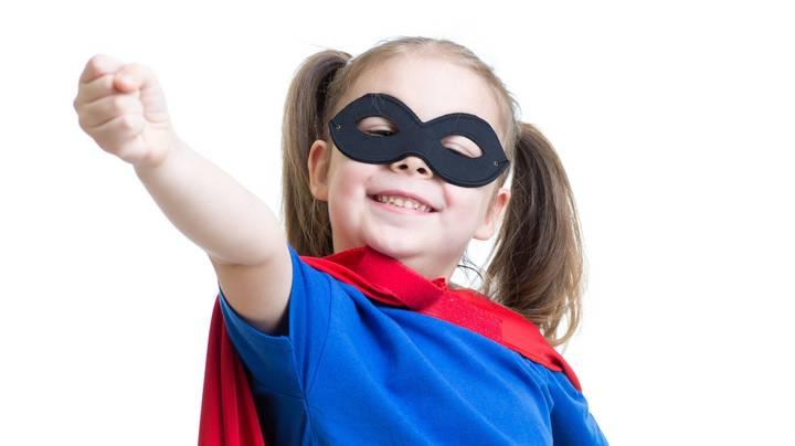 Kleines Mädchen mit rotem Umhang und Maske spielt Superheld