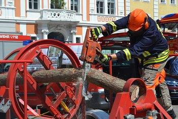 Feuerwehrmann demonstriert mit einer Kettensäge einen Trennschnitte im Baumbiegesimulator