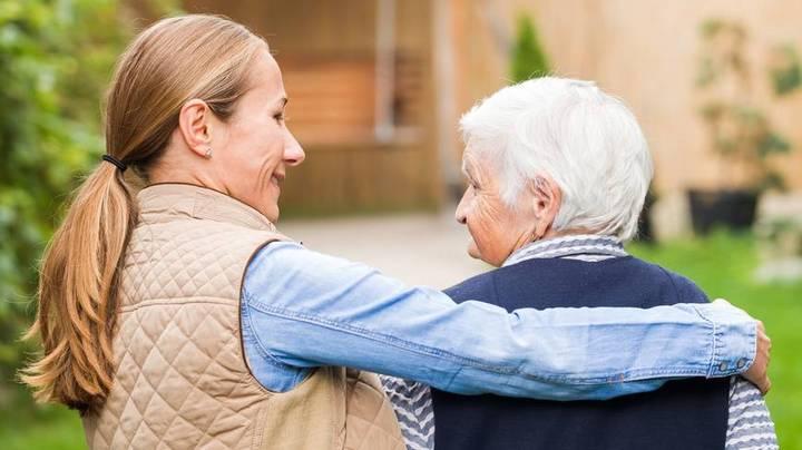Frau nimmt ihren älteren Vater in den Arm und lächelt ihn an.