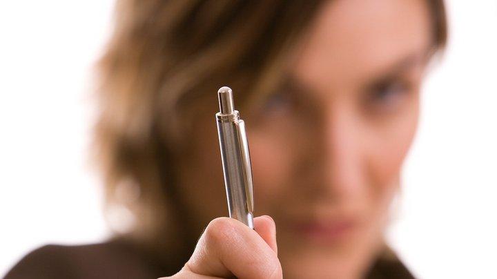 Eine Unternehmerin hält einen Kugelschreiber direkt in die Kamera