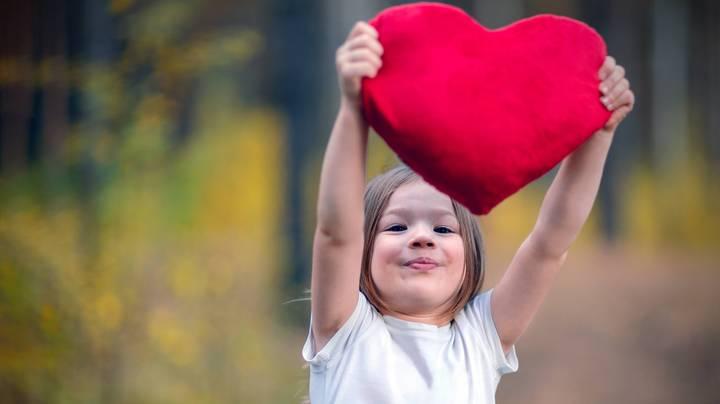 Ein kleines Mädchen hält ein rotes Herz aus Plüsch in die Höhe
