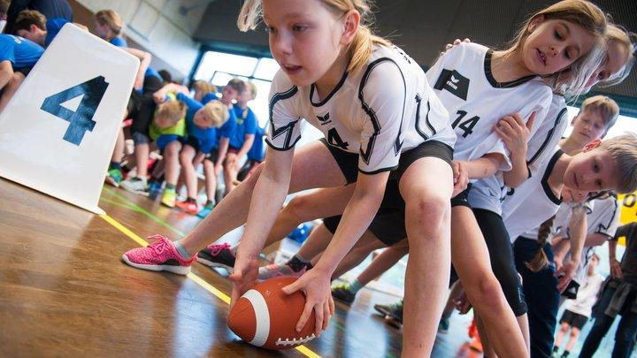 Schülerin übergibt beim Staffelwettbewerb  Football durch die Beine.