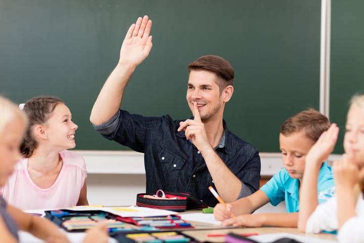 Lehrer zeigt den Schülern mit dem Zeigefinger vor dem Mund, dass sie leisen sollen und den Finger heben sollen, wenn Sie etwas sagen möchten