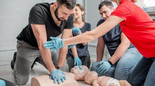 Eine Frau erklärt im Rahmen einer Schulung zur Ersten Hilfe einer Gruppe von Ersthelfern die Wiederbelebung. Ein Mann übt dazu an einer Puppe.