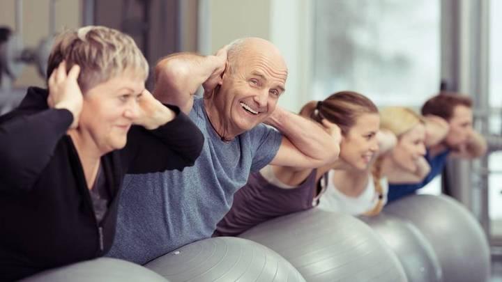 Älterer Beschäftigter macht Sport in der Gruppe