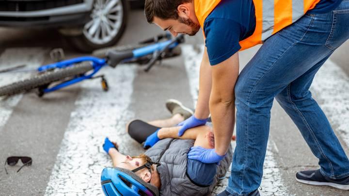 Ein Ersthelfender versorgt einen verletzten Radfahrer