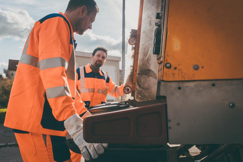 Zwei Arbeiter beladen Müllfahzeug
