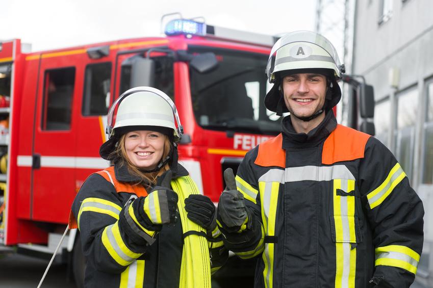 Zwei Feuerwehrleute in Einsatzkleidung vor Feuerwehrfahrzeug