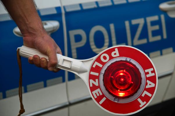 Polizeikelle vor Einsatzfahrzeug