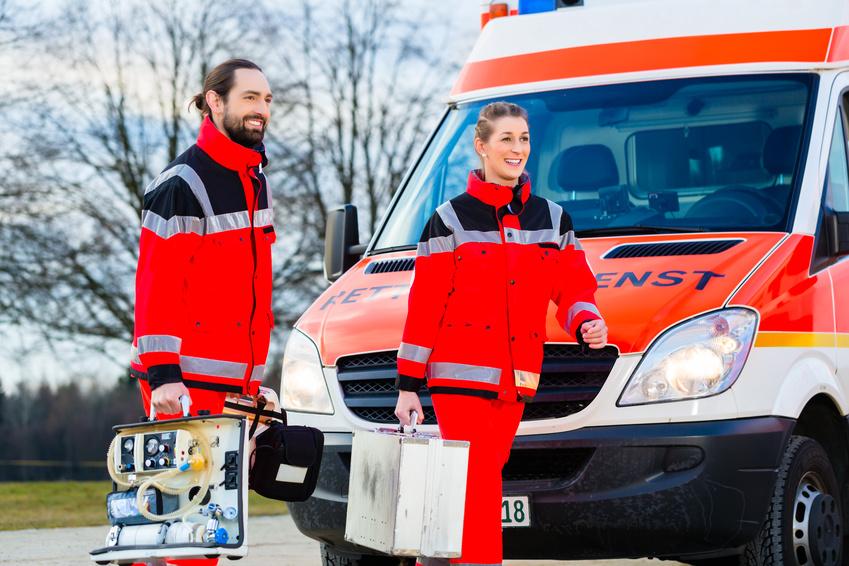 Zwei Rettungssanitäter vor Einsatzfahrzeug