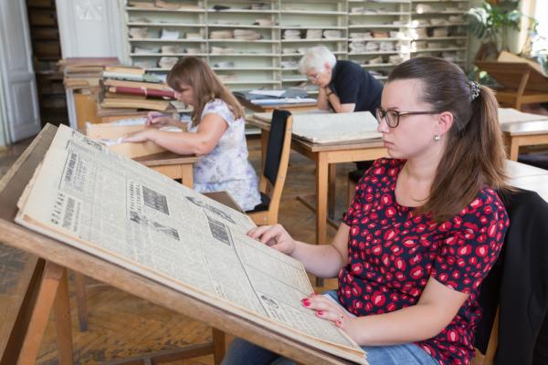 Frau liest eine alte Zeitung im Lesesaal eines Archivs